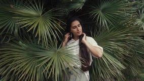 Un estudiante joven está en arboledas de la palma, una señora tiene en la alheña del mehendi de las manos y de los fingeres almacen de metraje de vídeo