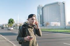 Un estudiante joven hermoso con una mochila que da un paseo alrededor de la ciudad y que escucha la música en los auriculares cer Fotos de archivo