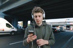 Un estudiante joven que escucha la música y que escribe un mensaje en el teléfono que aguarda transporte público En el fondo del  Imagen de archivo libre de regalías
