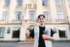 Un estudiante joven sonriente con una libreta en sus manos muestra su finger para arriba en el fondo de la entrada a la universid Foto de archivo libre de regalías