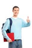 Un estudiante masculino que sostiene un libro y que da el pulgar para arriba Foto de archivo libre de regalías