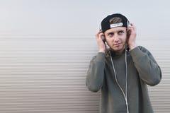 Un estudiante positivo es feliz de escuchar la música en auriculares en un fondo ligero Imagenes de archivo