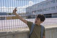 Un estudiante que descansa fuera de una escuela y que juega con un teléfono móvil Foto de archivo libre de regalías