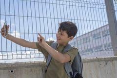 Un estudiante que descansa fuera de una escuela y que juega con un teléfono móvil Imagenes de archivo