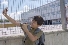 Un estudiante que descansa fuera de una escuela y que juega con un teléfono móvil Fotos de archivo libres de regalías