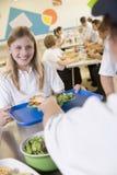 Un estudiante que recoge el almuerzo en cafetería de escuela Fotos de archivo libres de regalías