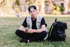Un estudiante que se sienta en la hierba en el parque del campus universitario y que usa un teléfono móvil en el fondo de un camp Fotos de archivo libres de regalías