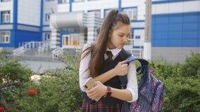Un estudiante se coloca delante de la escuela, la mamá envía SMS y pone el teléfono en la mochila Adolescencia de la muchacha des metrajes