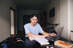 Un estudiante serio está estudiando en casa con un ordenador portátil en su sitio que se sienta en la tabla Preparación Una mirad Fotografía de archivo libre de regalías