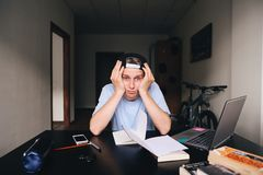 Un estudiante triste que se sienta en un escritorio del trabajo en una casa cerca de un ordenador portátil y de los libros Enseña Imagen de archivo libre de regalías