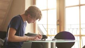 Un estudiante zurdo que se sienta en la tabla que hace su preparación, reflexión sobre las respuestas almacen de metraje de vídeo