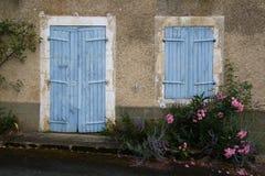 Un estudio de una puerta de madera azul vieja y de una ventana shuttered Fotografía de archivo libre de regalías