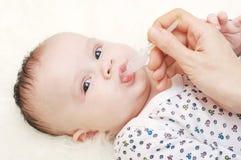 Un'età adorabile del neonato di 3,5 mesi che bevono succo Immagini Stock