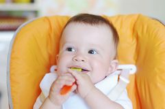 Un'età del bambino di 9 mesi con il cucchiaio sulla cucina Fotografia Stock Libera da Diritti
