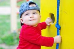 Un'età del bambino di 10 mesi sul campo da giuoco di estate Fotografie Stock