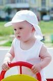Un'età del neonato di 9 mesi sul campo da giuoco all'aperto Immagine Stock Libera da Diritti