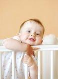Un'età divertente del bambino di 9 mesi in letto bianco Immagini Stock Libere da Diritti