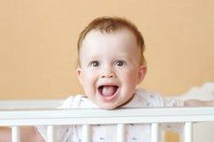 Un'età felice del bambino di 9 mesi in letto bianco Fotografie Stock