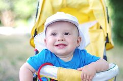 Un'età felice del bambino di 9 mesi su carrozzina gialla Immagine Stock