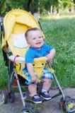 Un'età felice del bambino di 9 mesi sul carrozzino Immagini Stock