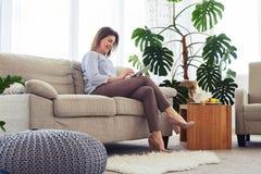 Un'età graziosa di signora di 35-45 che lavora in computer portatile mentre sedendosi sulla s Immagine Stock