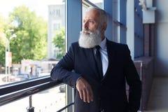 Un'età maschio Unsmiling di 50-60 che guarda fuori finestra Fotografia Stock Libera da Diritti