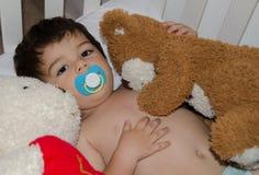 Un et demi bébé garçon d'années dans le berceau étreignant son ours de nounours images stock