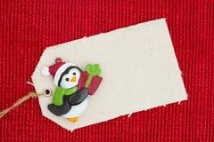 Un'etichetta del regalo del panno con un pinguino di Natale su materiale rosso brillante Fotografia Stock Libera da Diritti