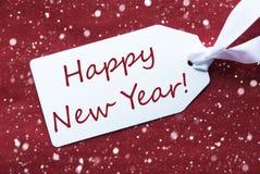Un'etichetta su fondo rosso, fiocchi di neve, buon anno del testo Immagini Stock