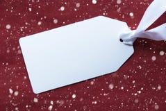 Un'etichetta su fondo, sui fiocchi di neve e sullo spazio rossi della copia Fotografia Stock Libera da Diritti