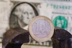 Un euro dans un vice dans la perspective du dollar américain image libre de droits