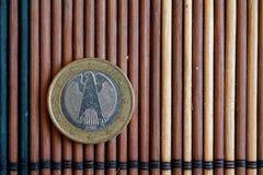 Un euro mensonge de pièce de monnaie sur la dénomination en bambou en bois de table est de 1 euro - arrière Photo libre de droits