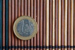 Un euro mensonge de pièce de monnaie sur la dénomination en bambou en bois de table est d'un euro Images libres de droits