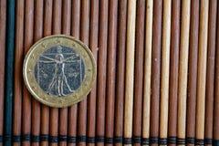 Un euro mensonge de pièce de monnaie sur la dénomination en bambou en bois de table est 2 l'euro - arrière Photos libres de droits
