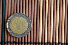 Un euro mensonge de pièce de monnaie sur la dénomination en bambou en bois de table est 2 l'euro - arrière Image libre de droits