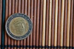 Un euro mensonge de pièce de monnaie sur la dénomination en bambou en bois de table est 2 l'euro - arrière Images libres de droits