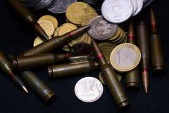 Un euro, rublo rusa y pequeñas monedas ucranianas con la munición militar del rifle en fondo negro Simboliza la guerra para el di foto de archivo libre de regalías