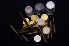 Un euro, rublo rusa y pequeñas monedas ucranianas con la munición militar del rifle en fondo negro Simboliza la guerra para el di imagenes de archivo