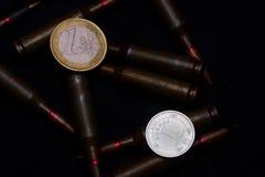 Un euro y el hryvna ucraniano acuña con la munición militar del rifle en fondo negro Simboliza la guerra para el problema más gra fotografía de archivo libre de regalías
