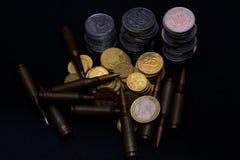 Un euro y pequeñas monedas ucranianas con la munición militar del rifle en fondo negro Simboliza la guerra para el problema más g fotos de archivo