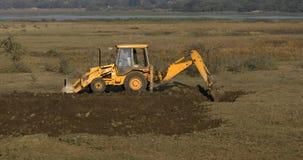 Un excavador o una niveladora que cava la tierra foto de archivo libre de regalías