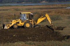 Un excavador o una niveladora que cava la tierra Fotos de archivo libres de regalías
