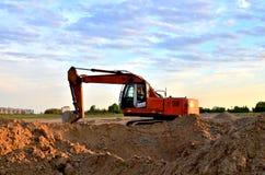 Un excavador pesado en un funcionamiento en la mina del granito descarga las piedras concretas viejas para que el machacamiento y fotografía de archivo libre de regalías