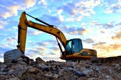 Un excavador pesado en un funcionamiento en la mina del granito descarga las piedras concretas viejas para que el machacamiento y fotografía de archivo