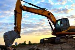 Un excavador pesado en un funcionamiento en la mina del granito descarga las piedras concretas viejas para que el machacamiento y imagen de archivo libre de regalías