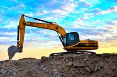 Un excavador pesado en un funcionamiento en la mina del granito descarga las piedras concretas viejas para que el machacamiento y fotos de archivo