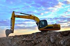 Un excavador pesado en un funcionamiento en la mina del granito descarga las piedras concretas viejas para que el machacamiento y foto de archivo libre de regalías