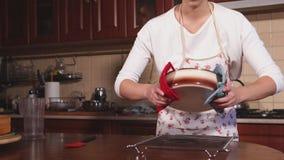 Un experto culinario joven saca las tortas recientemente cocidas de los platos para cocer almacen de video