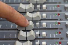 Un experto que ajusta la consola de mezcla audio Seleccione el foco Fotos de archivo libres de regalías