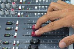 Un experto que ajusta la consola de mezcla audio Seleccione el foco Imagen de archivo